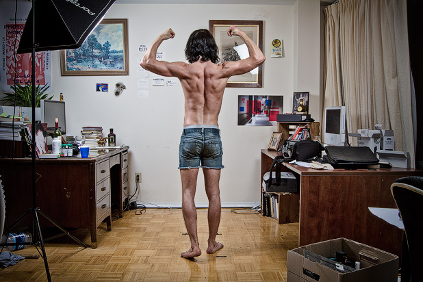 Skinny bodybuilder flexing his back muscles